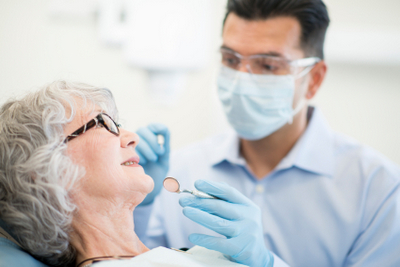 Older patient relaxing in a dental chair while her dentist prepares to examine her mouth